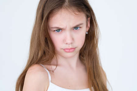emotion face. grumpy unhappy discontent child frowning. little girl portrait on white background. mood feelings personality and facial expression concept