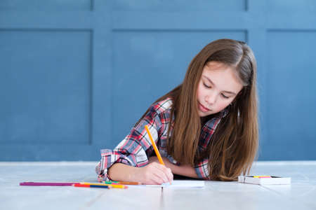 art drawing hobby. inspiration ideas and creative leisure. little girl lying on the floor and creating a picture with pencils.