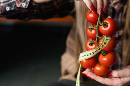 diet weightloss and fitness. organic natural food products for healthy eating. woman holding fresh tomatoes with twisted measuring tape in hand.