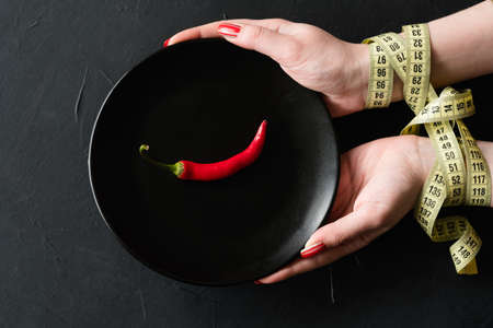 food deficiency. strict weightloss diet. unhealthy slimming methods. poorly balanced eating. woman hands tied with measuring tape holding a plate with single chili pepper Stock Photo - 105415845