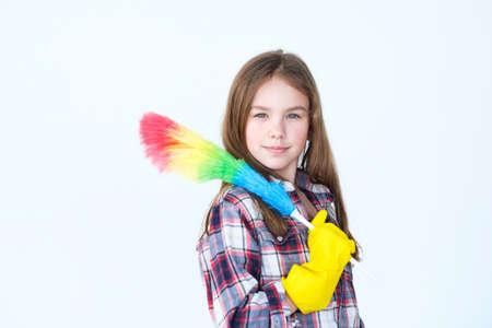 home cleaning and tidying up. household chores and domestic work. moms little helper. adolescent girl in yellow protective rubber gloves and a colorful duster on white background