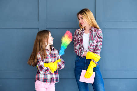 household duties and family combined efforts. mom and daughter ready for housekeeping and home cleaning. mother and kid armed with yellow rubber gloves and a duster Stok Fotoğraf
