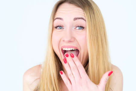 emotion face. amazed happy surprised overjoyed amused woman holding hand to mouth. young beautiful blond girl portrait on white background.