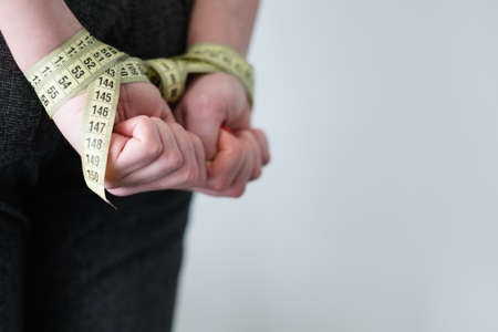 weightloss and slimming. body size and fitness. food deficiency and restraint concept. woman hands tied with measuring tape behind her back