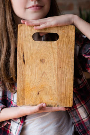 girl holding kitchen wooden cutting board. food cooking and preparation. meal recipe concept. empty space for advertising. Reklamní fotografie - 105507109