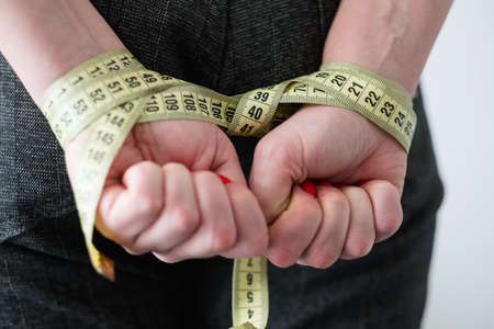 food deficiency. strict weightloss diet. unhealthy slimming methods. woman hands tied with measuring tape behind her back