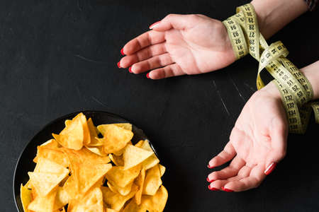 weightloss and fitness. natural food products for healthy eating. no chips snacks while dieting. woman hands tied with measuring tape. Stock Photo