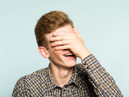 facepalm. happy smiling joyful man covering his face. shame and fun concept. portrait of a young guy on light background. emotion facial expression. 写真素材