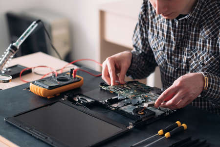 technology microelectronics science education. engineer student inspecting disassembled broken laptop and removing motherboard Stock Photo