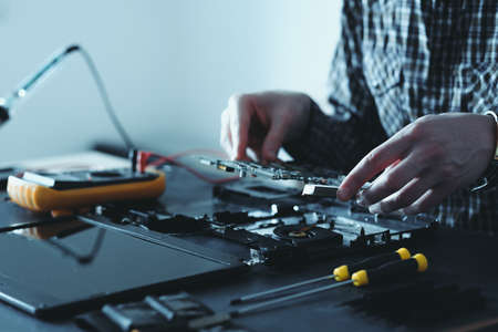 computer upgrade. technology development. microelectronics scientific innovation concept. engineer disassembling laptop Stock Photo