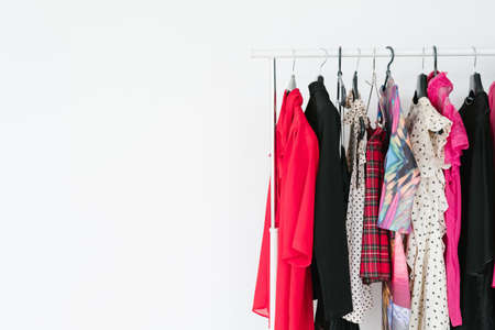 fashion and clothing. personal style and popular trends. self expression and creativity. selection of bright clothes hanging on the rack. white background with free space.