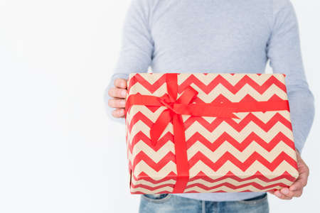 holiday present in a big gift box with red chevron pattern and a bow. christmas or new year festive season concept.