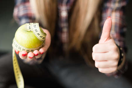thumb up for healthy food. diet nutrition and balanced eating. apple fruit for slim and fit body and weightloss