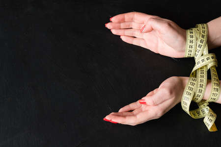 self control will power and restraint. dieting weightloss and fitness. woman hands tied with measuring tape.