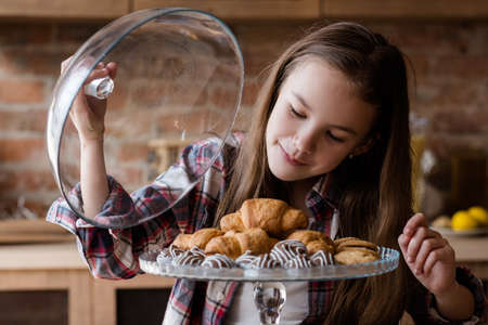 child unbalanced eating. unhealthy bad habits. confectionery and puff pastry overeating. little girl drooling over croissants and chocolate sweets Stok Fotoğraf