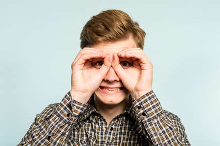 funny ludicrous joyful comic playful man pretending to look through binoculars. portrait of a young guy on light background. emotion facial expression. feelings and people reaction. 写真素材