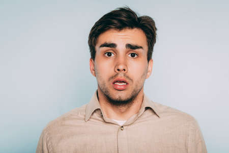 clueless shocked disoriented puzzled uncomprehending man. feeling at loss. portrait of a young brunet guy on light background. emotion facial expression. Stock Photo