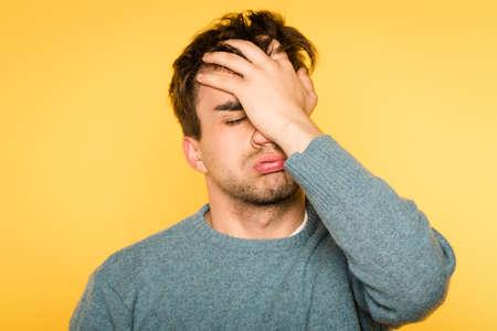 facepalm. wanhopige gefrustreerde man die zijn gezicht bedekt. hopeloze situatie en spijt. portret van een jonge donkerbruine kerel op gele achtergrond. emotie gezichtsuitdrukking en gevoelens concept.