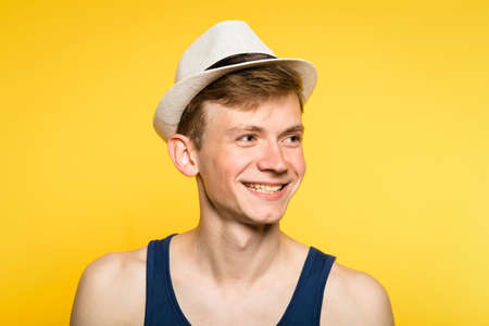cute smiling handsome young man in tank top and fedora. portrait of a young guy on yellow background. emotion facial expression. feelings and people reaction.