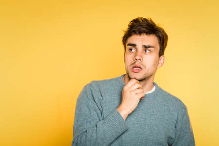 puzzled confused man scratching his beard thinking of smth. portrait of a young handsome brunet guy on yellow background. emotion facial expression. feelings and people reaction concept.