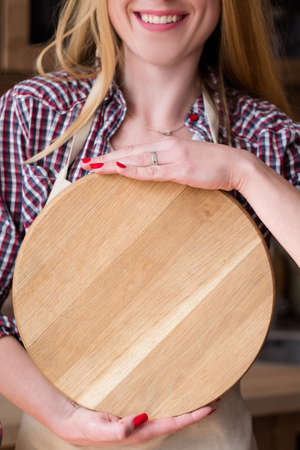 smiling woman holding round wooden cutting board. kitchen utensils and food preparation. meal recipe. empty space for advertising. circle template