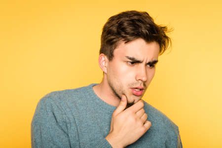 puzzled confused bewildered man scratching his beard thinking of smth. portrait of a young handsome brunet guy on yellow background. emotion facial expression and feelings concept. Reklamní fotografie