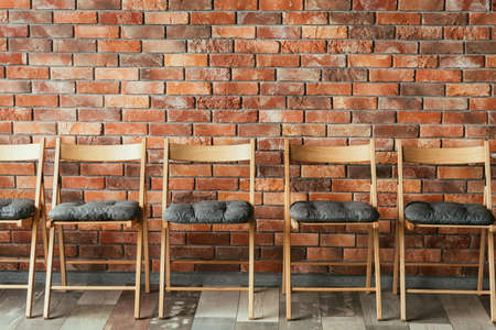 line of empty chairs on the brick wall loft background. vacant seat. concept of waiting area or job interview session. competition rivalry and promotion.