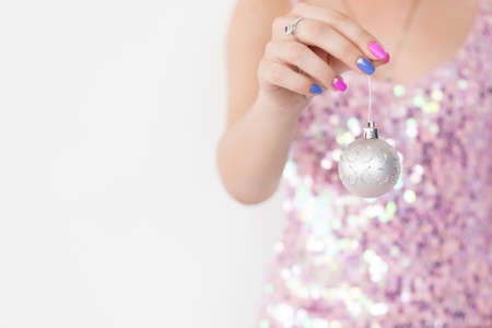christmas ball. elegant festive decor and new year holiday ornamens concept. woman holding silver glittery bauble in hand. free space on white background.
