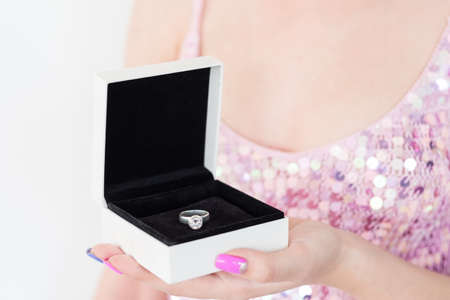 symbol of love and commitment. woman holding diamond engagement ring in a gift box. marriage and strong relationship concept.