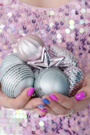 christmas balls. elegant festive decor and new year holiday ornaments concept. woman holding handful of silver glittery baubles.