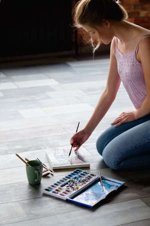 creative leisure. painting hobby. artful personality. talented girl drawing a picture sitting on the floor.