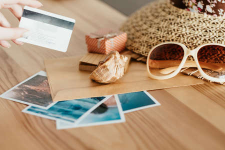 money loan for summer vacation. holidays traveling and resort destinations concept. woman holding a credit bank card. sun hat sunglasses and seaside photos on the desk.