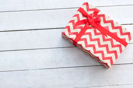 gift box with red chevron pattern and a bow on white background. holiday present and worthy reward on anniversary birthday of christmas. celebration and festive season concept. 스톡 콘텐츠
