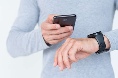 modern technology and helpful applications and devices. mobile phone and smart watch symbiosis. useful accessory on man's wrist. Foto de archivo