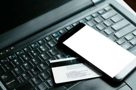 technologies mobiles de gestion de l'argent en ligne. des outils et des applications numériques pratiques pour contrôler vos finances. carte bancaire de crédit ou de débit et smartphone sur l'ordinateur portable. écran de téléphone blanc blanc. Banque d'images