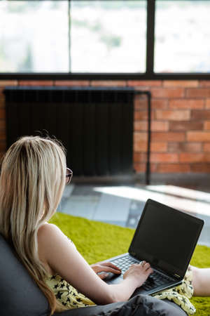 social media influencer and marketing. blogger working on laptop adding a new content to her profile. smm and e-business advertising concept. Stock Photo