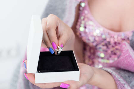 engagement happiness and couple relationship. woman taking out expensive diamond ring from a gift box.