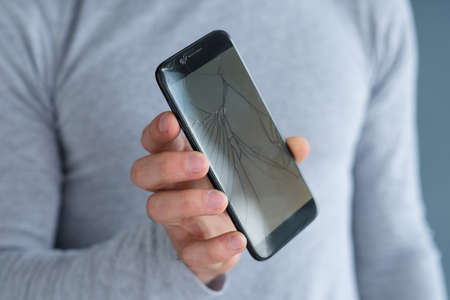 smashed shattered cracked screen. man holding damaged smart phone. mobile devices repair service concept.