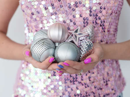 christmas balls. elegant festive decor and new year holiday ornaments concept. woman holding handful of silver toys glittery baubles pines and a star. Stock Photo
