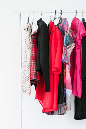 stylish woman wardrobe. colorful selection of fashionable clothes. assortment of bright trendy clothing on a rack. 스톡 콘텐츠