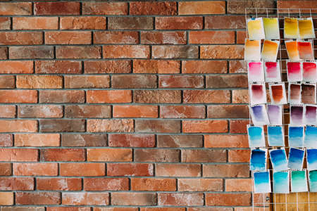 watercolors swatch assortment on loft brick wall. ink dyes colors mix on paper. art painting and drawing. inspiration and creativity. artist skills practice. free space concept.