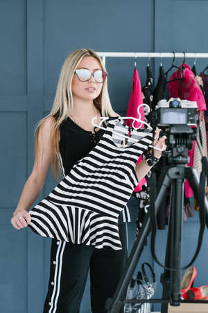 modern fashion beauty trends explained by a stylish professional. woman holding a stripy top in hands and shooting a video.