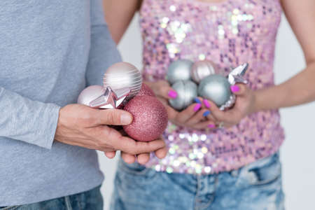 christmas balls. elegant festive decor and new year holiday ornaments concept. focus on man holding handful of rose gold glittery baubles. woman in the background holding silver spheres. Stock Photo