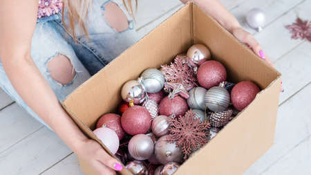 christmas and new year decoration traditions. woman holding a box with glittery balls and toys. festive embellishments concept
