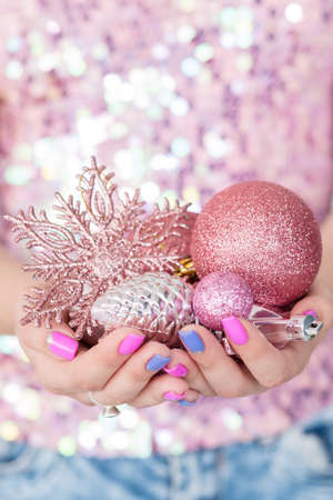 christmas balls. elegant festive decor and new year holiday ornaments concept. woman holding handful of rose gold glittery baubles.