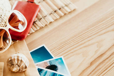 summer vacation on the beach. traveling tourism and holidays concept. sunglasses seashell and photos on wooden desk. memories experiences and adventures.