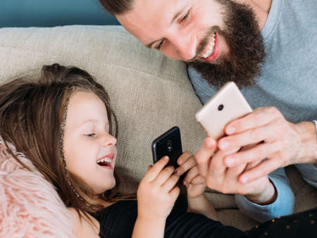 happy family leisure and gratifying rewarding fatherhood. dad and daughter sharing a laugh together after seeing a funny pic or video online. father and kid using mobile phone. 版權商用圖片