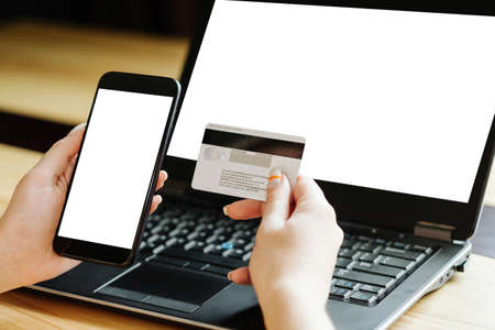 secure online payments. two factor authorization. woman hands holding bank card and mobile phone. white blank laptop screen for e-commerce. Banco de Imagens
