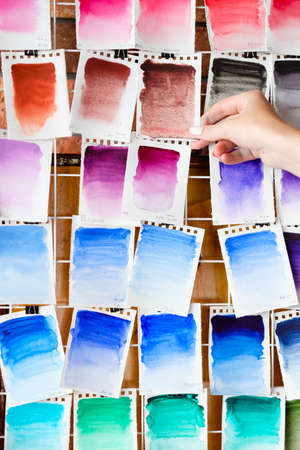 watercolors swatch assortment background. ink dyes colors mix on paper. art painting and drawing. inspiration and creativity. artist skills practice. free space concept. woman hand choosing.