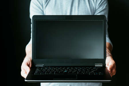 online education. internet training programs. learning new profession remotely. computer technology and global connection concept. man holding a laptop with empty black screen.